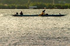 Os pescadores são pôr a armadilha dos peixes no lago Fotos de Stock Royalty Free