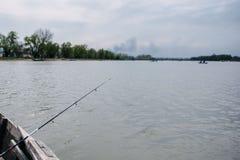Os pescadores travam os peixes que sentam-se no barco imagens de stock