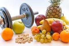 Os pesos e os frutos sortidos e a medida gravam o conceito saudável da perda de peso do estilo de vida Fotografia de Stock
