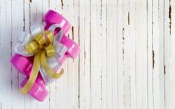 Os pesos e o presente cor-de-rosa do esporte curvam-se no fundo de madeira branco, mim Foto de Stock