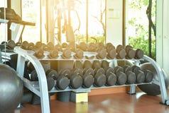 Os pesos encontram-se em seguido na cremalheira do inventário no gym ou no fitness center fotografia de stock royalty free