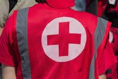 Os pessoais médicos no uniforme com o sinal da cruz vermelha fornecem o auxílio médico Fotografia de Stock Royalty Free