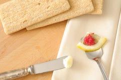 Os petiscos luxuosos, a faca elegante para a manteiga e o lumpfish vermelho eggs em uma colher Foto de Stock