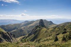 Os picos rochosos dramáticos ajustaram-se contra uma cordilheira e um céu azul Foto de Stock Royalty Free