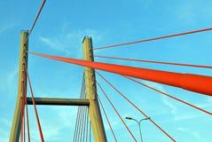 Os pilões da ponte nas cordas contra o céu azul nas nuvens Foto de Stock Royalty Free