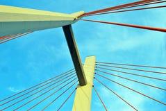 Os pilões da ponte nas cordas contra o céu azul nas nuvens Fotos de Stock