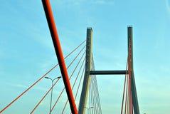 Os pilões da ponte nas cordas contra o céu azul nas nuvens Imagens de Stock