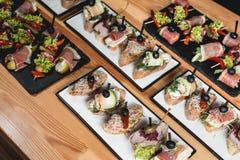 Os pinchos saborosos com atum, chouriços, salmões, ovo, secaram tomates, abacate, salmão, bacon, Hamon, Brie Cheese, azeitonas e Imagens de Stock