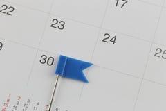 Os pinos azuis colocaram no calendário ao lado do número de trinta Imagem de Stock