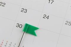 Os pinos verdes colocaram no calendário ao lado do número de trinta Imagens de Stock