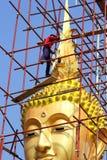 Os pintores estão pintando a estátua dourada grande da Buda Foto de Stock