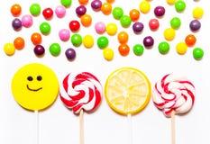 Os pirulitos, sorriso dos doces sobre, dispersaram em volta dos comprimidos Imagens de Stock