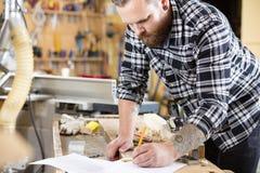 Os planos do carpinteiro trabalham e tomam notas no desenho do projeto Fotografia de Stock Royalty Free