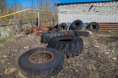 Os pneus e o veículo podres abandonados rodam dentro a sucata fotografia de stock