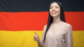 Os polegares-acima mostrando fêmeas asiáticos bonitos assinam contra o fundo alemão da bandeira filme
