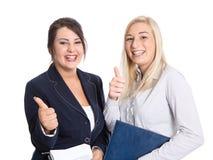 Os polegares bem sucedidos dos bussineswomen levantam e sorrindo no branco Fotos de Stock Royalty Free