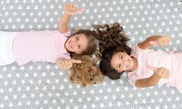 Os polegares da mostra das crianças levantam o gesto Crianças das meninas na opinião superior da cama Conceito do partido de pija imagem de stock royalty free
