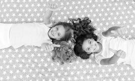 Os polegares da mostra das crianças levantam o gesto Crianças das meninas na opinião superior da cama Conceito do partido de pija foto de stock