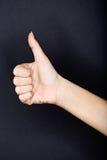 Os polegares fecham-se acima acima no fundo preto Fotos de Stock