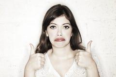 Os polegares sarcásticos levantam a mulher triste foto de stock
