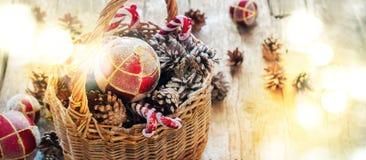 Os pontos claros brilhantes como o efeito festivo com a árvore de abeto do Natal brincam na cesta, bolas vermelhas, cones do pinh Fotos de Stock