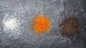 Os pontos salgam, o açafrão, pimenta em uma pedra cinzenta Fotos de Stock