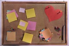 Os post-it vazios customizáveis e o coração vermelho dão forma no quadro de mensagens da cortiça Imagens de Stock