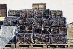 Os potenciômetros das cestas das redes dos cestos da lagosta empilham a pilha em cestas da rede de pesca dos fishermans do porto fotografia de stock