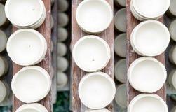 Os potenciômetros de argila brancos feitos a mão secam em pranchas de madeira Vista superior Oficina, manufactory imagem de stock