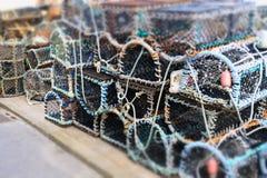 Os potenciômetros de peixes da lagosta e do caranguejo pescaram as caixas empilhadas no porto fotos de stock