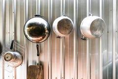 Os potenciômetros e as bandejas penduraram acima em uma cozinha tailandesa imagens de stock