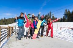 Os povos agrupam com Snowboard e mãos de ondulação alegres de Ski Resort Snow Winter Mountain Fotos de Stock Royalty Free