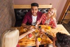 Os povos agrupam comer a batata dos hamburgueres do fast food que senta-se na tabela de madeira na opinião de ângulo superior do  Imagem de Stock