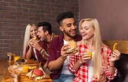 Os povos agrupam comer os hamburgueres do fast food que sentam-se na tabela de madeira no café Imagem de Stock