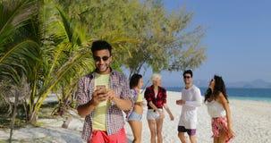 Os povos agrupam na praia, hispânico Guy Using Cell Smart Phone que conversa dança em linha, do homem e das mulheres filme