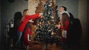 Os povos alegres da família de quatro pessoas estão decorando a árvore e o sorriso de Natal filme