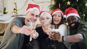 Os povos alegres da raça misturada têm o divertimento que guarda copos de vinho com champanhe antes do Natal ou do ano novo em ca vídeos de arquivo