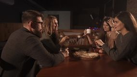 Os povos alegres estão rindo no café, guardando vidros com bebidas alcoólicas video estoque