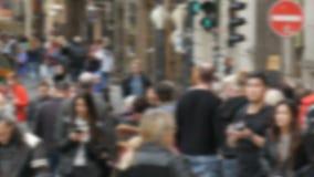 Os povos anônimos ocupados fora de foco estão andando A multidão de povos no megapolis cruza a rua e passa-se filme