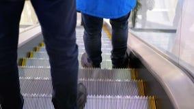 Os povos anônimos que andam na escada rolante levantam no shopping vídeos de arquivo