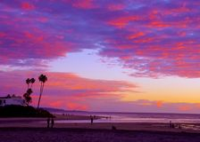 Os povos andam ao longo da praia com entrada maré que apreciam um por do sol glorioso, Del Mar, Califórnia imagens de stock