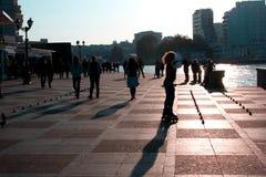 Os povos andam ao longo do passeio na cidade do mar no por do sol fotografia de stock