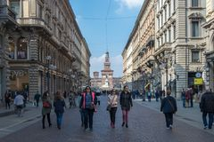 Os povos andam na rua através de Dante no fundo o castelo de Sforzesco, Itália foto de stock royalty free