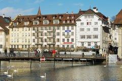 Os povos andam pela ponte com as construções históricas no fundo na lucerna, Suíça Fotos de Stock Royalty Free