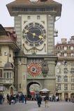 Os povos andam pela rua com a torre histórica de Bern Clock no fundo em Berna, Suíça Foto de Stock