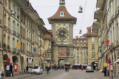 Os povos andam pela rua com a torre histórica de Bern Clock no fundo em Berna, Suíça Fotografia de Stock