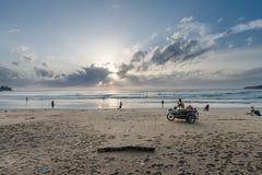 Os povos apreciam o por do sol tropical na praia Imagens de Stock