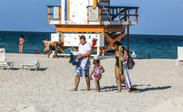 Os povos apreciam a praia ao lado de uma torre da salva-vidas fotografia de stock