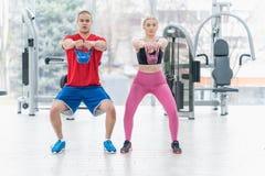 Os povos atrativos dos esportes dos jovens estão treinando no gym fotos de stock