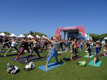 Os povos aumentam os braços largamente e espalham os pés durante a classe exterior da ioga Fotografia de Stock Royalty Free